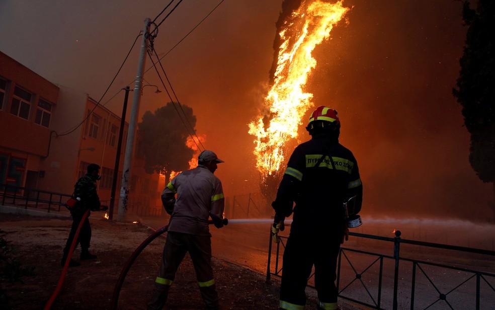 Bombeiros e militares combatem chamas na cidade de Rafina (Foto: Costas Baltas/Reuters)