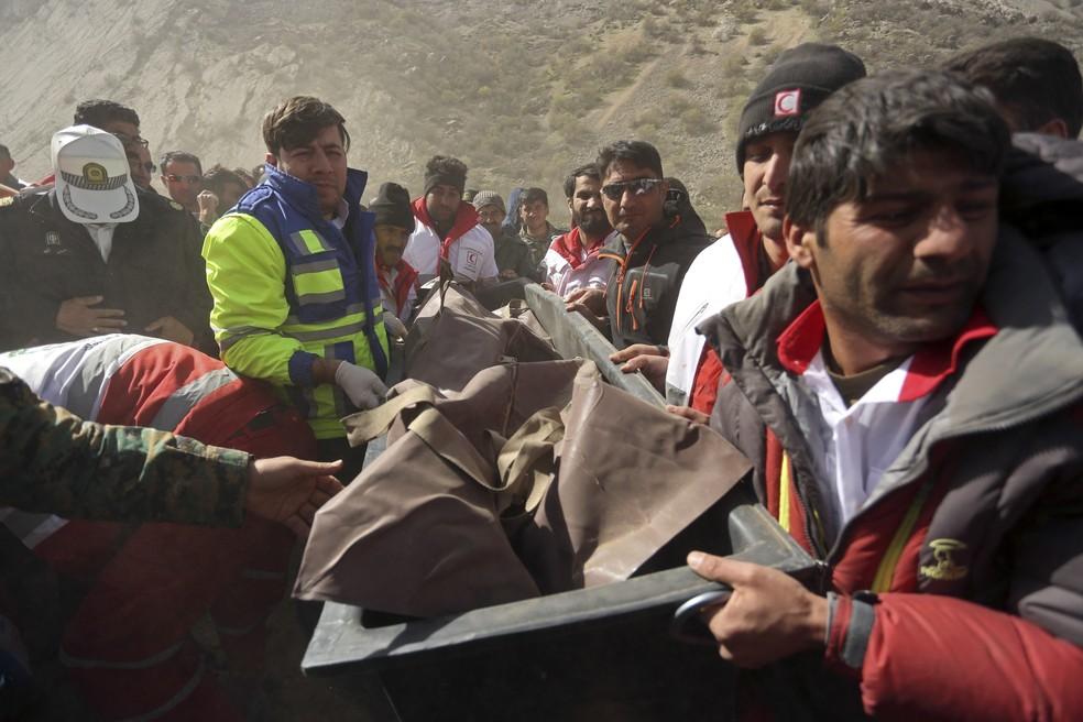 Equipes de resgate carregam corpo de vítima da queda de avião turco no Irã (Foto: Morteza Salehi/Tasnim News Agency via AP)