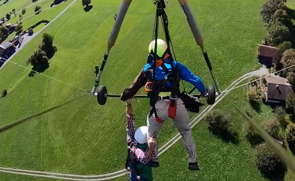 Turista precisou se segurar na perna do instrutor e na barra usada para conduzir a asa-delta — Foto: Chris Gursky/Youtube/Reprodução