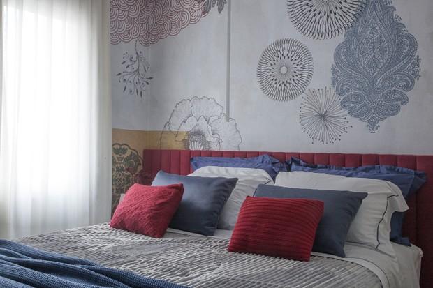 cabeceira vermelha e papel de parede estampado dão vida ao quarto