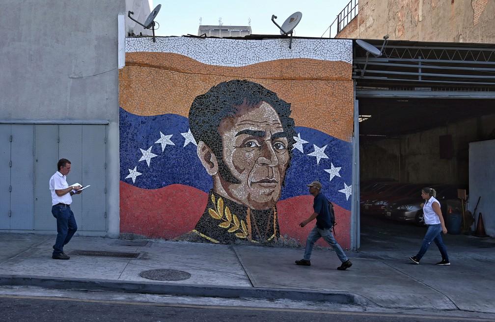 Pessoas passam por mural com a pintura de Simón Bolívar, em Caracas, na quarta-feira (15)  — Foto: Pedro Ugarte / AFP