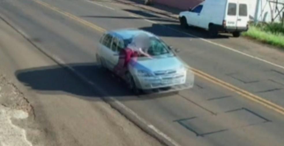 Mulher foi flagrada em cima de carro em movimento, em Francisco Beltrão, na terça-feira (13)  Foto: Câmeras de segurança