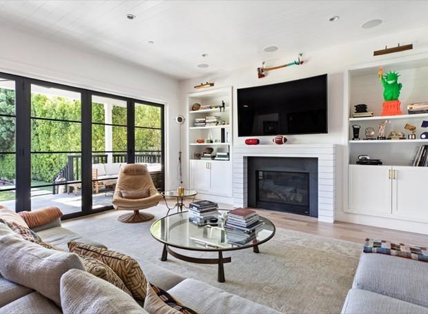 Uma sala de televisão é aquecida pela lareira e iluminada através das portas grandes (Foto: Variety/ Reprodução)