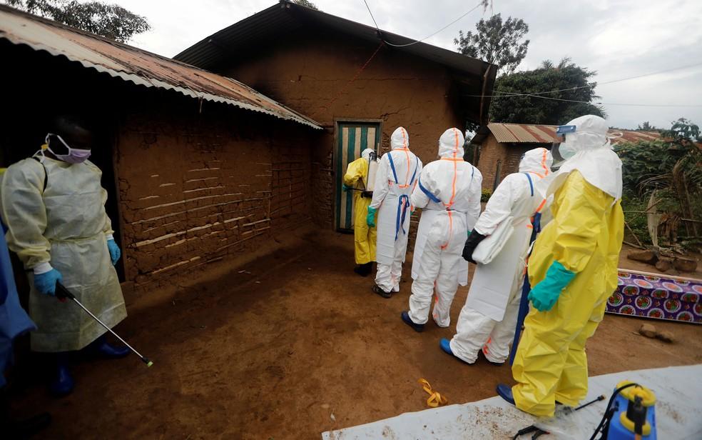 Kavota Mugisha Robert (esquerda), voluntário na força de resposta ao ebola, é visto com equipamento de descontaminação enquanto seus colegas se preparam para entrar em casa de paciente com suspeita da doença, em Beni, na República Democrática do Congo, em foto de 8 de outubro de 2019 — Foto: Reuters/Zohra Bensemra/File Photo