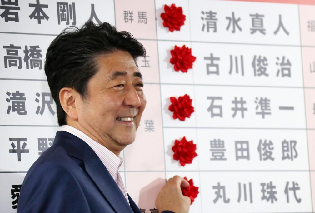 Primeiro-ministro japonês, Shinzo Abe, sorri neste domingo (21) diante das rosas vermelhas colocadas diante dos nomes dos candidatos vencedores do seu partido, o Liberal Democrata, das eleições para a Câmara Alta em Tóquio   — Foto: Koji Sasahara/AP