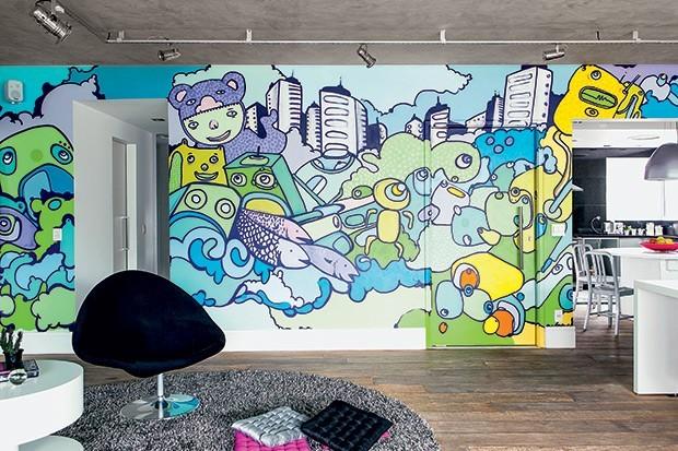 Grafite de Jey percorre não apenas a parede entre sala e cozinha, como avança sobre a porta pivotante que dá acesso ao hall do elevador  (Foto: Edu Castello/Casa e Jardim)