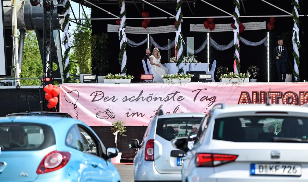 5 de maio - O casal de noivos Janine e Philip espera no palco o prefeito Thomas Geisel durante seu casamento em um cinema Drive-in de Duesseldorf, na Alemanha. O local começou a registrar casamentos permitindo que parentes e amigos participem de seus carros, pois os casamentos no cartório são limitados devido à pandemia de coronavírus — Foto: Martin Meissner/AP