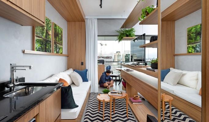 Estante funciona como divisora de ambientes em apartamento de 32 m²