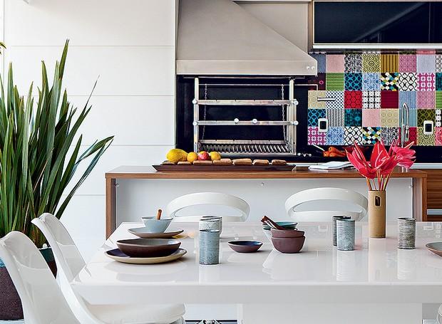Para compor a área da churrasqueira, a arquiteta Lucilene Leitte escolheu a mesa quadrada e o banco de resina com futon brancos. A brancura do espaço é quebrada pelos azulejos estampados e pela madeira de demolição do tampo da bancada (Foto: Edu Castello/Casa e Jardim)
