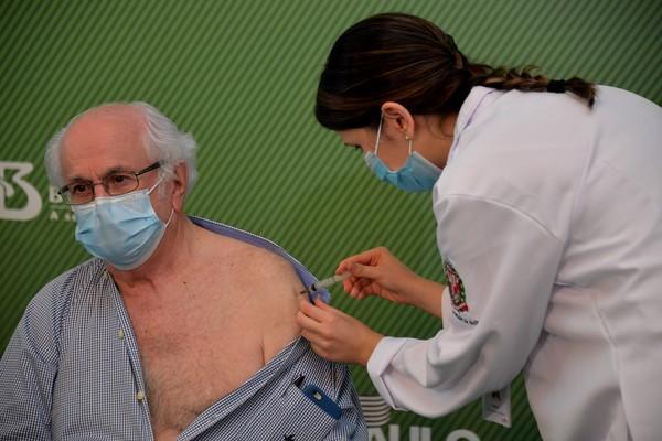 O médico Almir Ferreira de Andrade, de 79 anos, recebe a vacina CoronaVac contra a Covid-19 no Hospital das Clínicas, em São Paulo, neste domingo (17) — Foto: Nelson Almeida/AFP