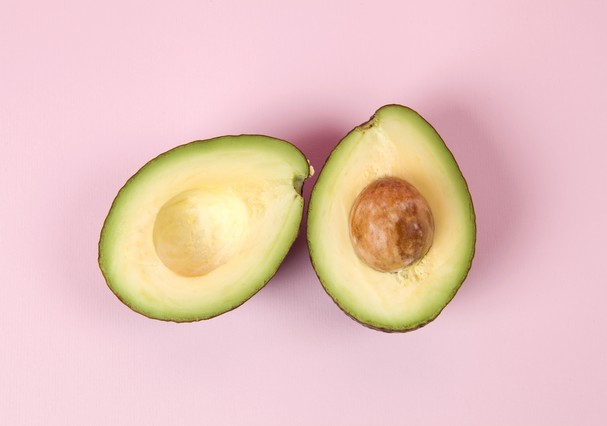 two avocado half with seed on a pink background. minimal color still life photography (Foto: Getty Images/iStockphoto)