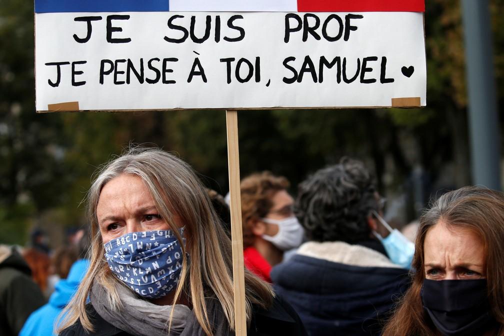 """'Eu sou professora. Eu penso em você, Samuel"""", diz cartaz em uma das manifestações na França em homenagem a professor decapitado por extremista — Foto: Pascal Rossignol/Reuters"""