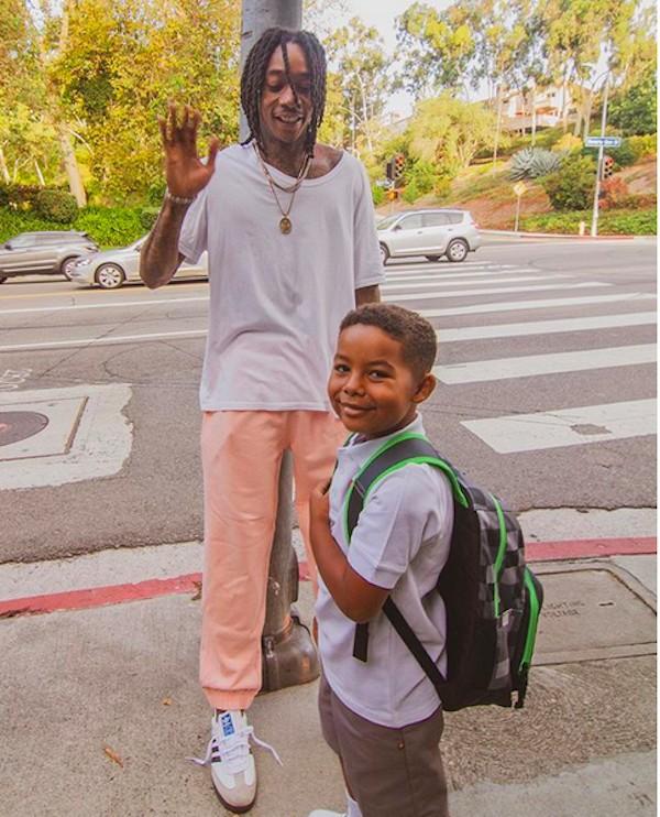 O rapper Wiz Khalifa esperando a chegada do ônibus escolar do filho (Foto: Instagram)