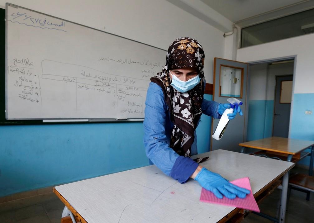 Funcionária desinfeta mesa de escola fechada como precaução contra o Covid-19 em Beirute, no Líbano, na terça-feira (3). — Foto: Mohamed Azakir/Reuters