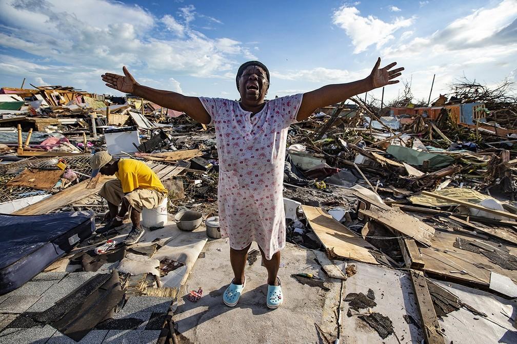 A haitiana Aliana Alexis abre os braços em desespero em meio ao que sobrou da estrutura de sua casa após a passagem do furacão Dorian em área chamada de 'The Mud' ('A Lama') em Marsh Harbour, na ilha de Great Abaco, nas Bahamas. O furacão de categoria 5 com ventos de quase 300 km/h deixou 20 mortos e graves inundações — Foto: Al Diaz/Miami Herald via AP