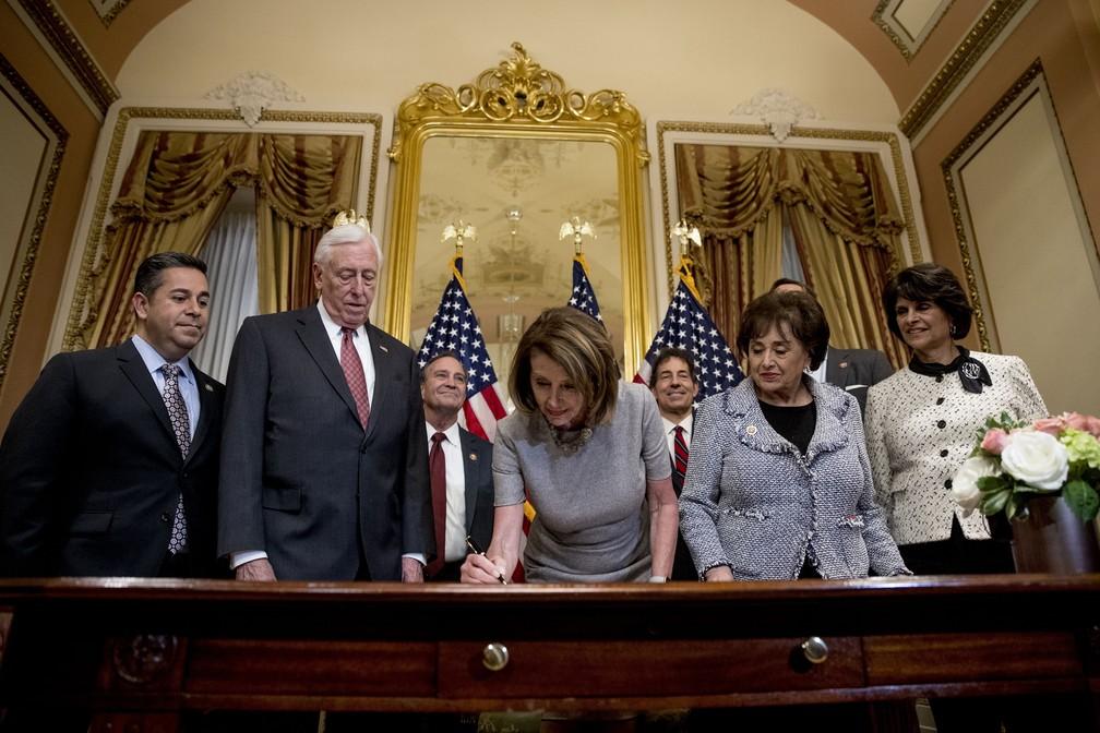 A presidente da Câmara dos Representantes, Nancy Pelosi, assina acordo para encerrar paralisação parcial do governo até 15 de fevereiro, ao lado de congressistas nesta sexta-feira (25) no Capitólio — Foto: Andrew Harnik/AP Photo