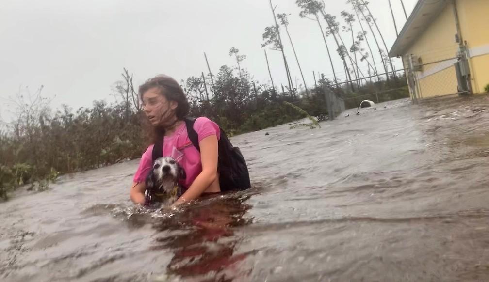 Julia Aylen atravessa as ruas alagadas carregando seu cachorro de estimação enquanto é resgatada de sua casa inundada durante passagem do furacão Dorian, em Freeport, nas Bahamas — Foto: Tim Aylen/AP
