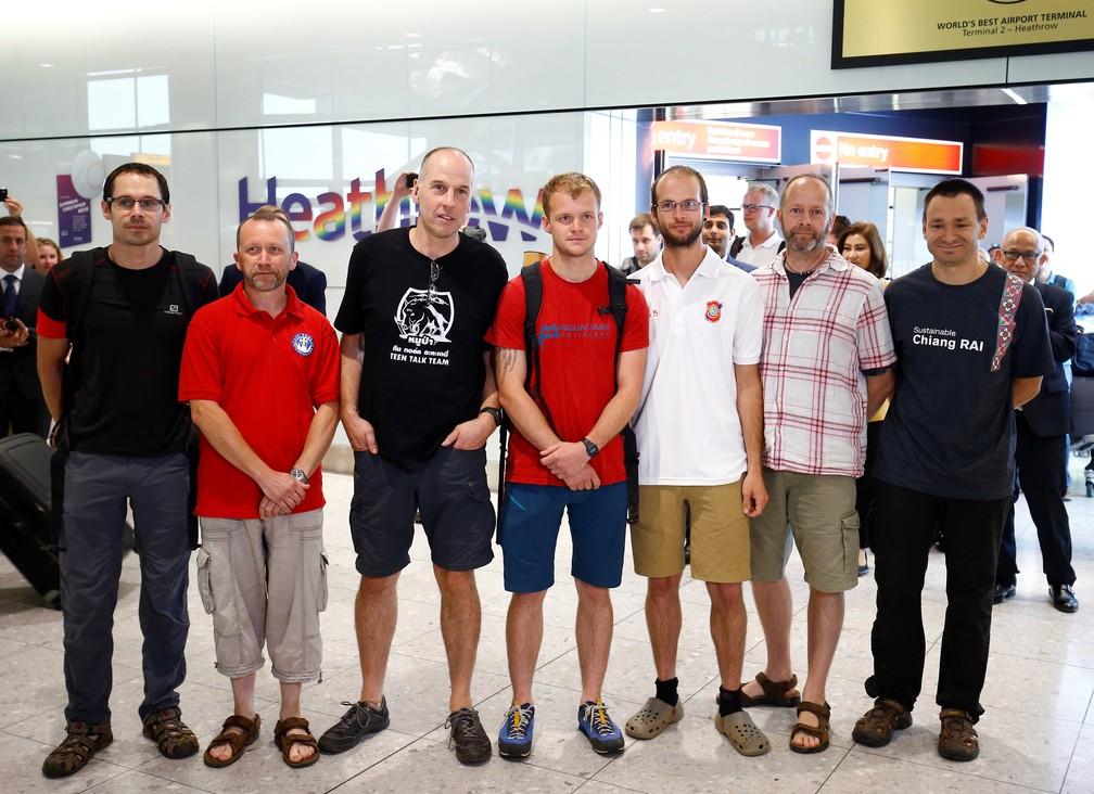 Mergulhadores que atuaram no resgate de jovens de caverna na Tailândia chegam nesta sexta-feira (13) no Aeroporto de Heathrow, em Londres. Da esquerda para a direita: Rick Stanton, Chris Jewell, Connor Roe, Josh Bratchley, Jim Warny, Mike Clayton e Gary Mitchell (Foto: Henry Nicholls/Reuters)