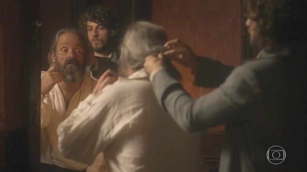 Joaquim (Chay Suede) arruma Olinto (Daniel Dantas) para que  o padre finja ser um comandante português, em 'Novo Mundo' — Foto: TV Globo