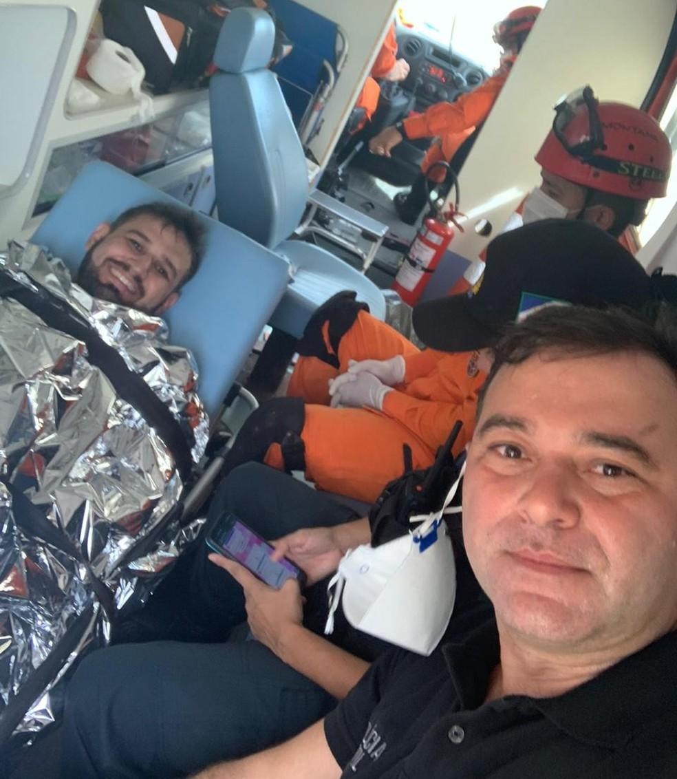 Jornalista Romano dos Anjos sorri em selfie com o delegado geral da Polícia Civil, Herbert Amorim, dentro da ambulância dos Bombeiros após sequestro — Foto: Arquivo pessoal