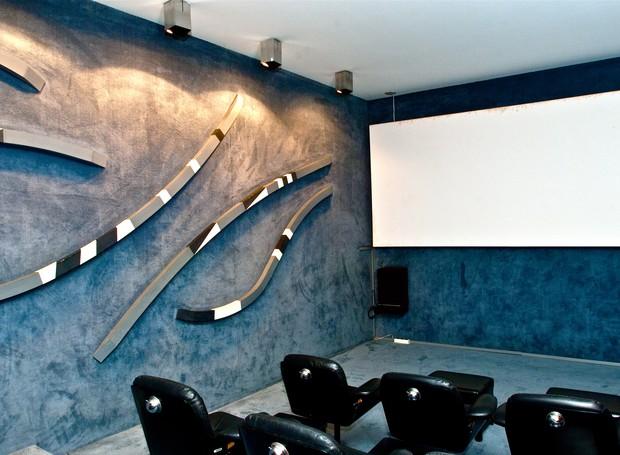 Vista interna do cinema: na parede revestida com carpete acústico, obra em madeira pintada de Athos Bulcão (Foto: Ichiro Guerra/Reprodução)