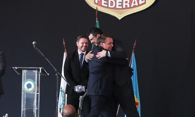 O papiloscopista João Paulo Dondelli abraça Bolsonaro ao lado do agente Danilo Campetti, todos sem máscara, durante solenidade da PF em outubro de 2020