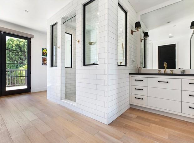 No banheiro, dois chuveiros ficam reclusos em cabines (Foto: Variety/ Reprodução)