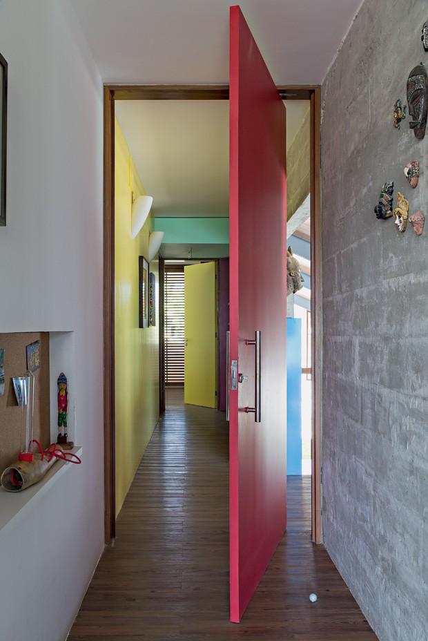 Circulação | As cores definem os ambientes. No corredor, a porta da suíte principal é vermelha, e a da outra suíte é amarela, assim como a parede (Foto: Fotos e produção Projeto Sertões)