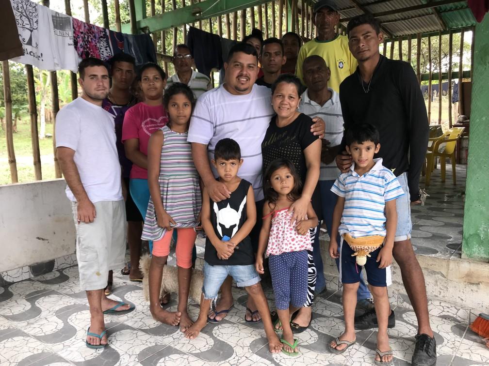 Gedeão (no centro) ao lado da esposa, Sandra, e parte dos refugiados que receberam após ataques (Foto: Emily Costa/G1 RR)