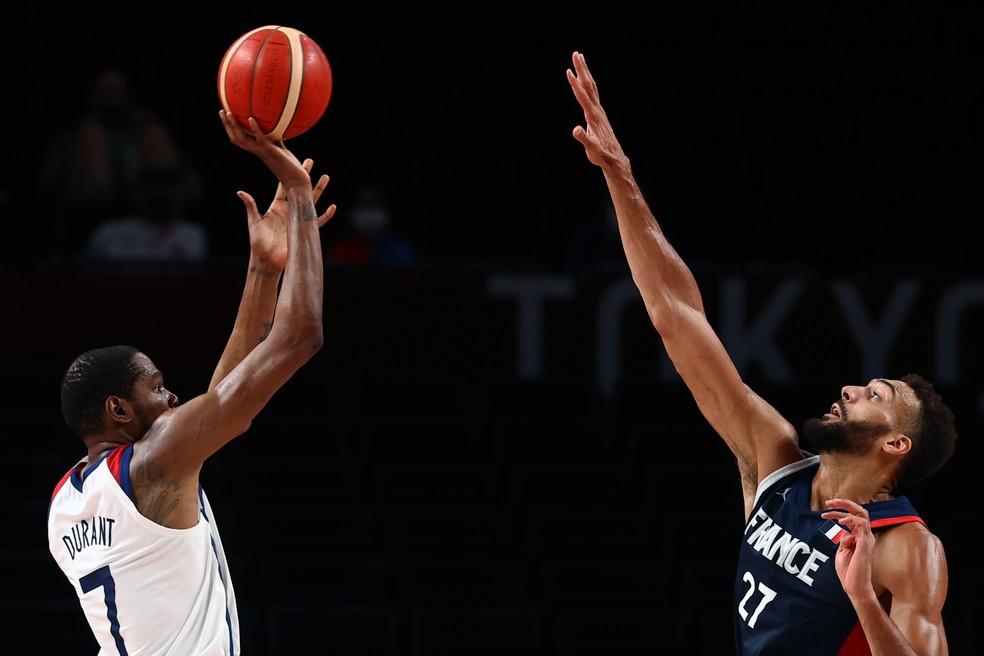 Kevin Durant (esq.) chuta de 3 pontos com Gobert (dir.) correndo para contestar o arremesso — Foto: REUTERS/Sergio Perez