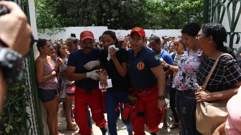 Bombeiros civis amparam Géssica Nascimento, mãe das duas crianças assassinadas pelo padrasto em Moreno, no Grande Recife — Foto: Aldo Carneiro/Pernambuco Press