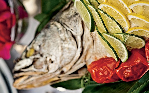 Robalo assado na folha de bananeira com tomates e farofa de banana-da-terra