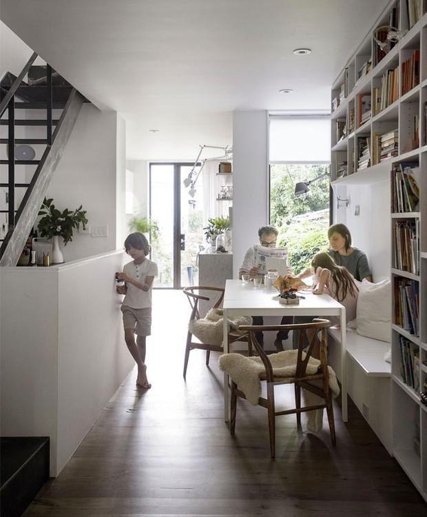 A casa é construída na vertical. Uma grande estante fica sobre a mesa de jantar, que está conectada à cozinha (Foto: Indecora/ Reprodução)
