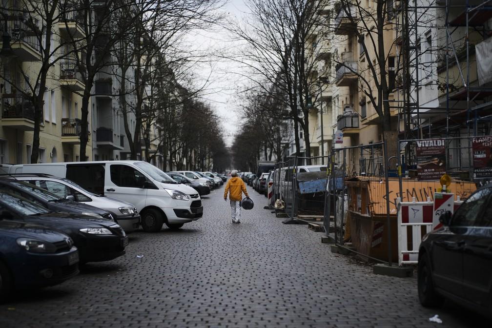 Um artesão solitário caminha sobre uma rua quase vazia no distrito Prenzlauer Berg, em Berlim, Alemanha, na terça-feira (17) — Foto: Markus Schreiber/AP