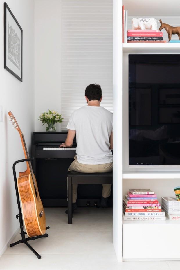 Música. O som do piano invadiu a casa e mostrou toda a sensibilidade do arquiteto. Repare que o escritório fica atrás de uma estante vazada, ótima ideia para um bom aproveitamento de espaço (Foto: Lufe Gomes / Editora Globo)