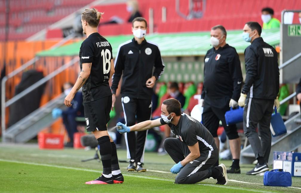 Não é desinfecção, mas atendimento médico contra lesão à beira do campo de Tin Jedvaj, do Augsburg, em partida contra o Wolfsburg — Foto: Tobias Hase/Pool via REUTERS DFL