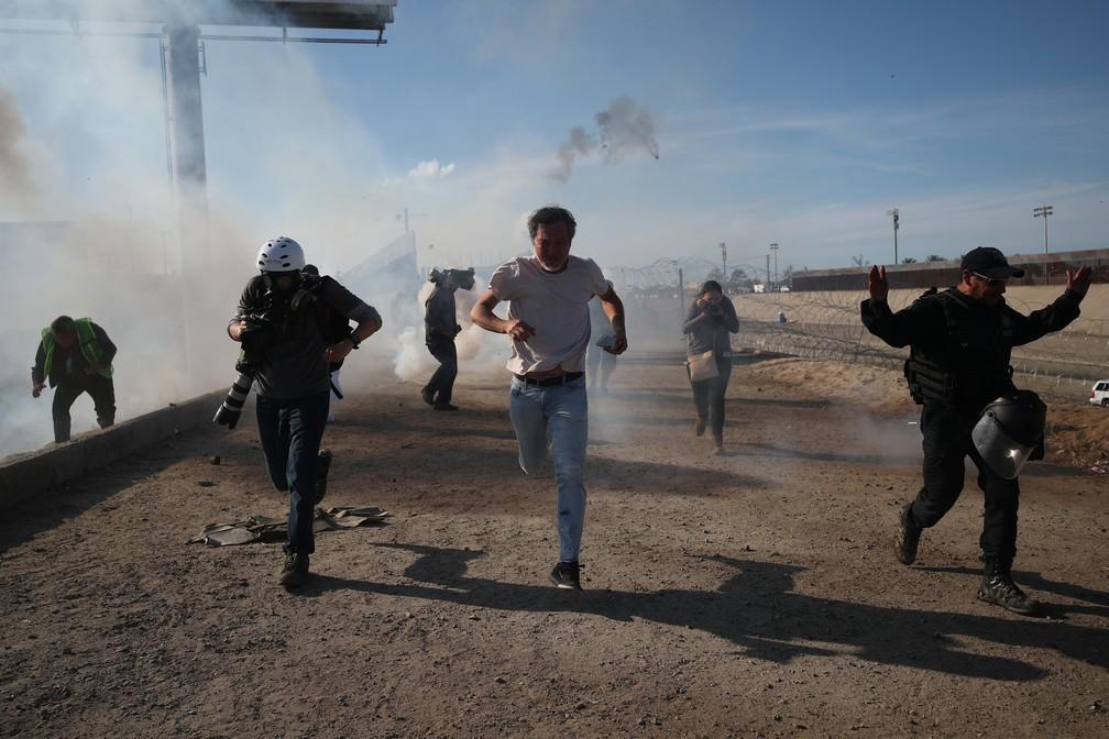 Oficiais dos EUA tentam conter imigrantes com gás lacrimogêneo — Foto: Reuters