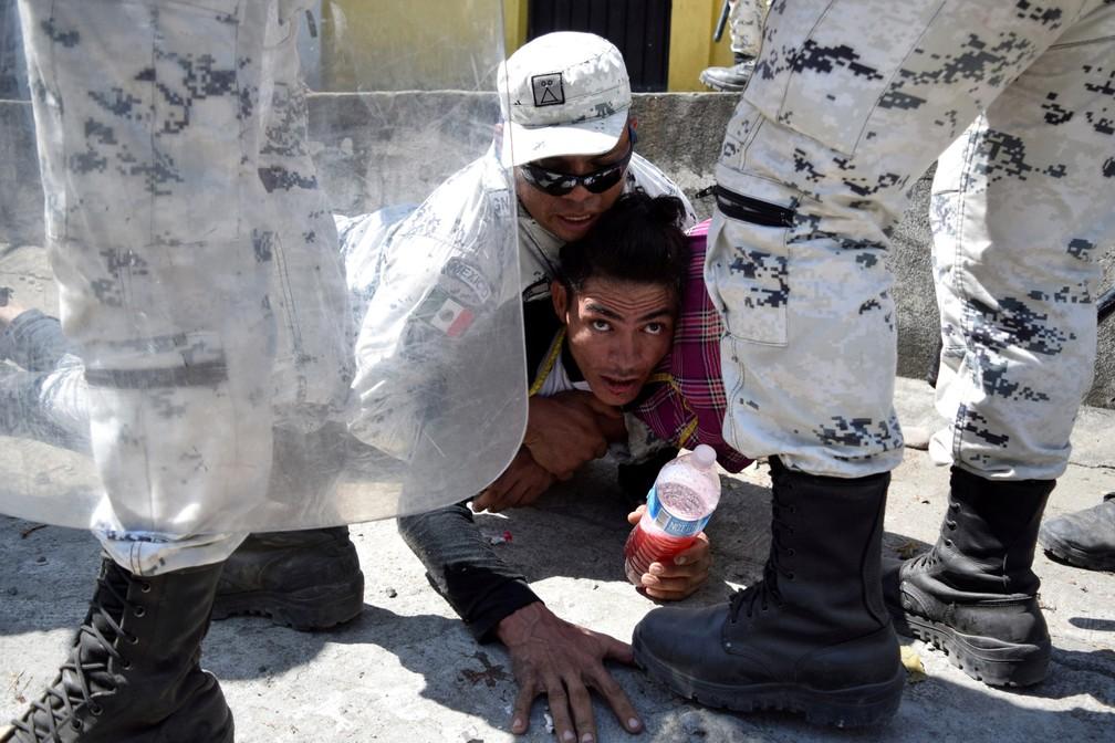 Um membro da Guarda Nacional do México detém um migrante, parte de uma caravana que viaja para os EUA, perto da fronteira entre a Guatemala e o México, em Ciudad Hidalgo, no México, em 20 de janeiro  — Foto: Jose Torres/Reuters