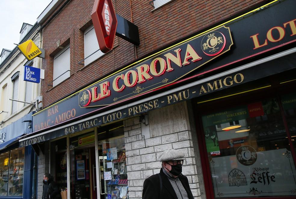 Homem com máscara de proteção passa em frente a uma tabacaria chamada Le Corona, em Croix, no norte da França, em foto de 28 de outubro — Foto: Michel Spingler/AP