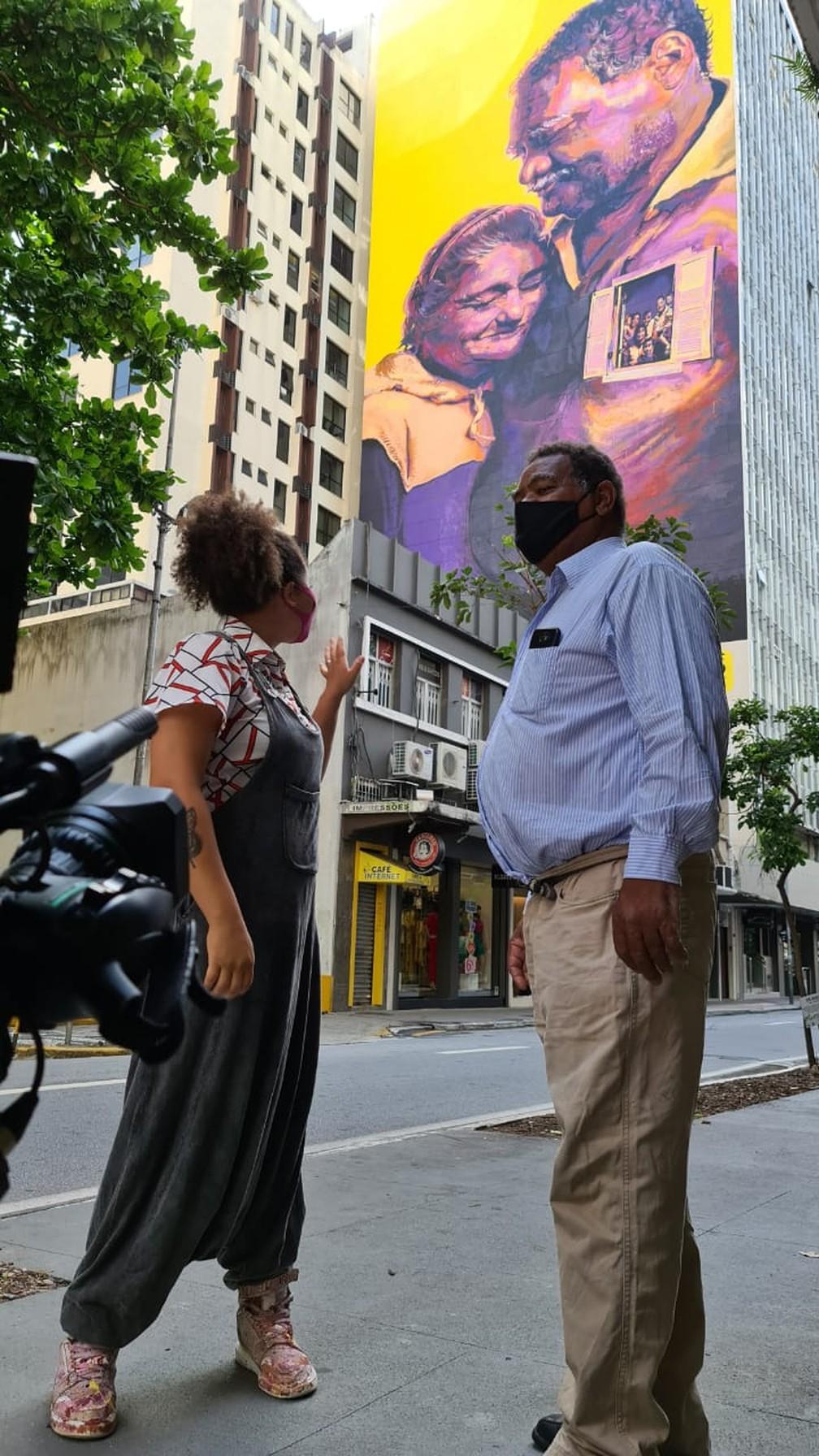 Gugie e Mário em frente ao painel de 700 m² no Centro de Florianópolis — Foto: Edson Amaral/ NSC TV