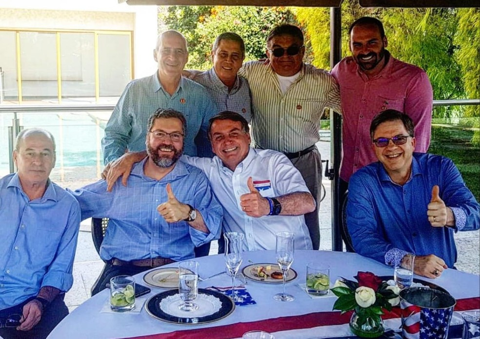 O presidente Jair Bolsonaro com o embaixador Todd Chapman (sentado, à direita), além de ministros e o filho Eduardo Bolsonaro, em almoço de comemoração da independência dos Estados Unidos — Foto: Reprodução