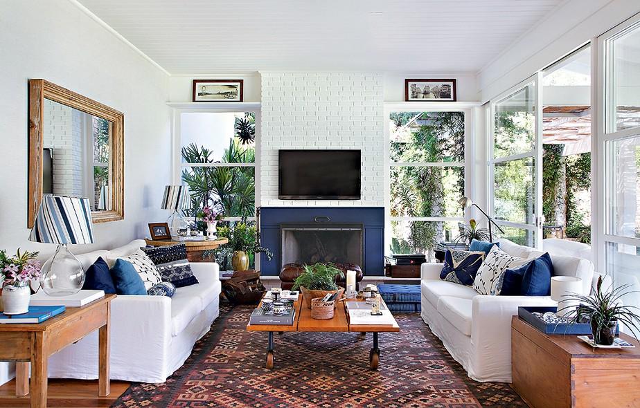 Nesta sala de TV bem iluminada, quem se destaca é o azul, que deixa o ambiente elegante e clássico, mas nem um pouco monótono! As almofadas em branco e azul são um charme no projeto da arquiteta Patricia Carvalho.