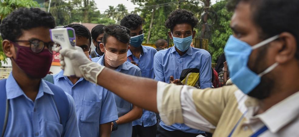 Estudantes com máscaras passam por higienização das mãos e checagem de temperatura na chegada para a aplicação de um exame estadual durante a pandemia do coronavírus em Kochi, no estado de Kerala, suld a Índia — Foto: R S Iyer / AP Photo