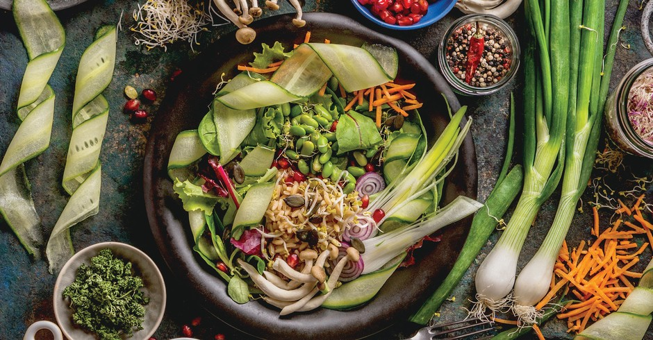 Healthy vegan lunch bowl making. Detox beautiful Buddha bowl with various fresh vegetables, edamame beans, mushrooms, seasoning and pumpkin seeds and nuts topping on rustic table with ingredients. Top view. Food flat lay (Foto: Getty Images)