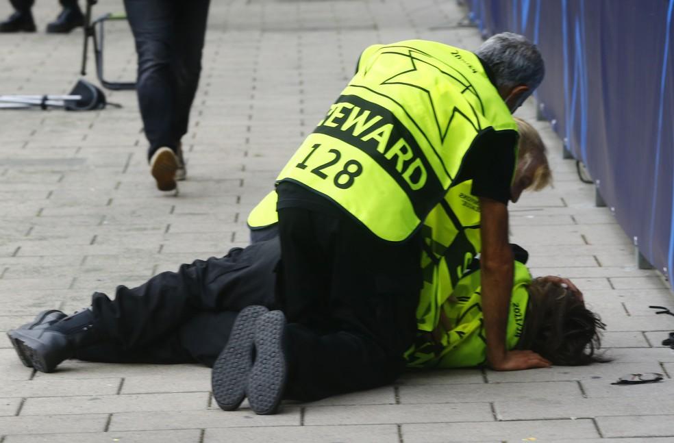 Steward estirada no chão assistida por dois colegas depois de levar bolada de Cristiano Ronaldo no aquecimento de Young Boys x Manchester United — Foto: REUTERS/Arnd Wiegmann