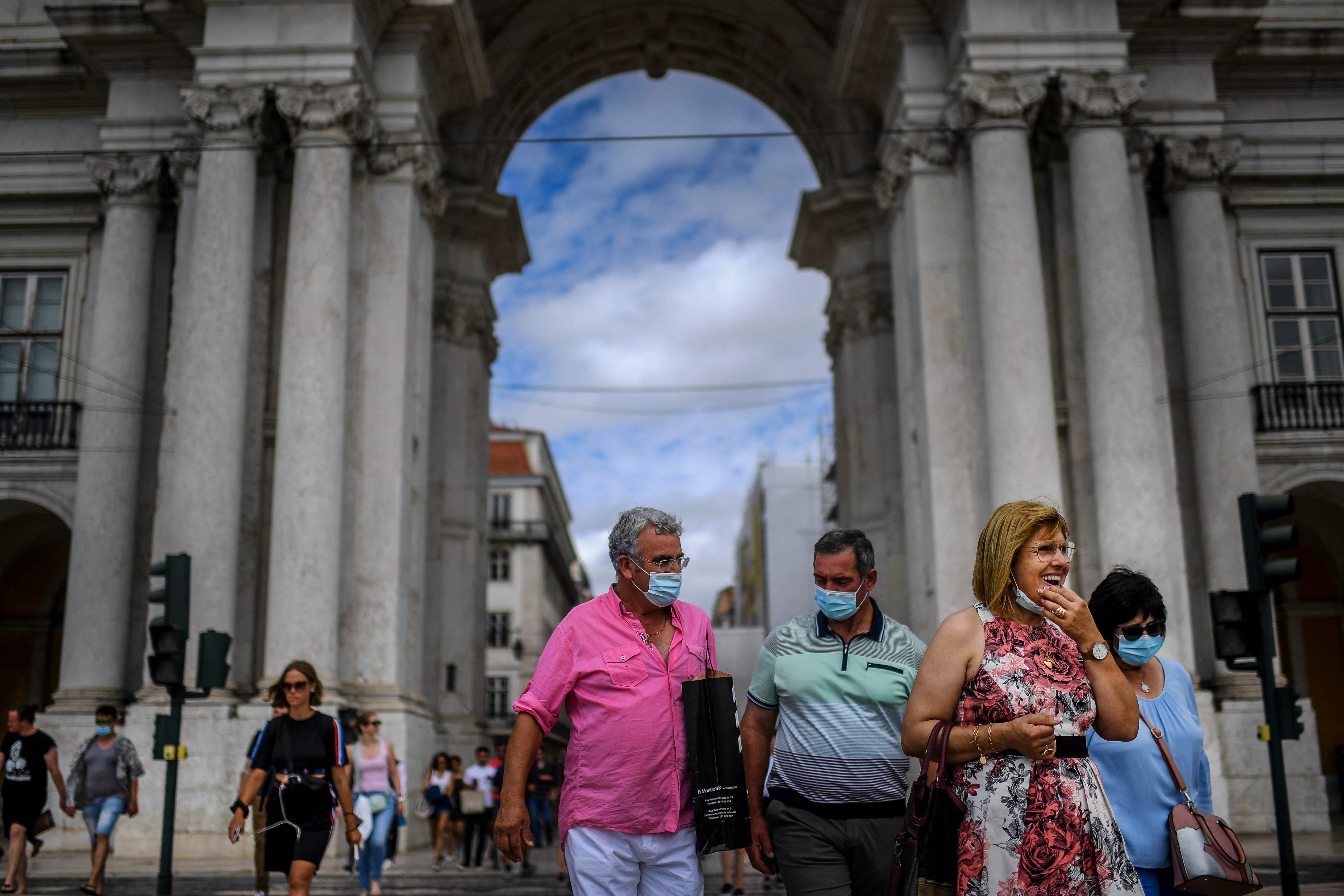 Pedestres em frente ao arco da Rua Augusta, em Lisboa