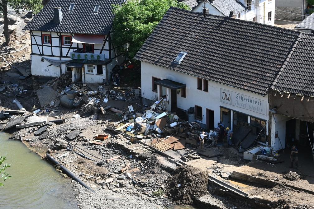 Imagem aérea mostra pessoas removendo escombros de uma carpintaria atingidas por enchente em Schuld, perto de Bad Neuenahr-Ahrweiler, no oeste da Alemanha, em 18 de julho de 2021 — Foto: Christof Stache/AFP