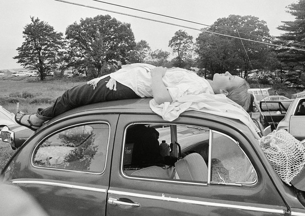 Mandatory Credit: Photo by Anonymous/AP/Shutterstock (6654316a)A girl naps on top of her car, while trying to reach the music festival at Woodstock, N.YWoodstock, New York, USA (Foto: Anonymous/AP/Shutterstock)