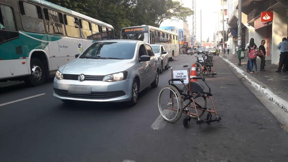 Cadeiras de rodas com placas escrito 'É repidinho' e outras frases foram colocadas em trecho de estacionamento na região central de Uberlândia — Foto: Fábio Melo/G1