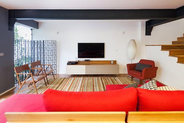 A poltrona é do Estúdio Paulo Alves. O sofá e o rack abaixo da televisão são do  Fernando Jaeger Atelier, e a luminária é da Reka. (Foto: Pedro Vannucchi)
